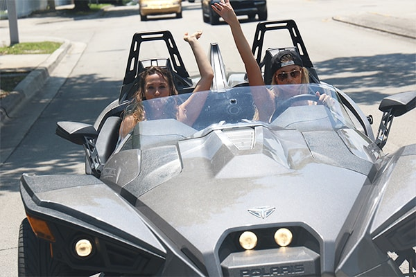 girls driving a slingshot in South Beach, Florida